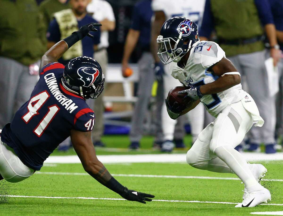 HOUSTON, TEXAS - NOVEMBER 26: Dion Lewis #33 of the Tennessee Titans avoids the tackle attempt by Zach Cunningham #41 of the Houston Texans during the first quarter at NRG Stadium on November 26, 2018 in Houston, Texas.