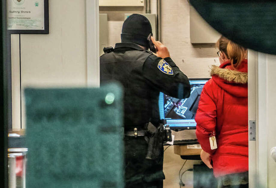 An Alton police officer review video surveillance video inside Kay Jewelers, 1702 Homer Adams Parkway, Monday night after the store had reportedly been robbed by a hammer-wielding man. Photo: Nathan Woodside | The Telegraph