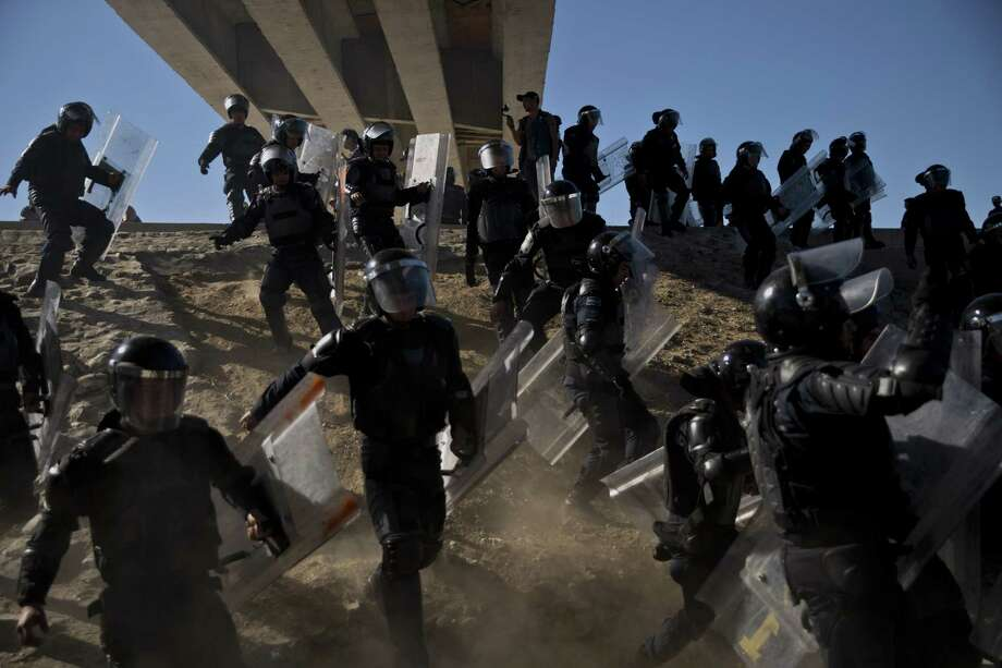 Policías mexicanos corren para intentar detener a migrantes en Tijuana, México, el domingo 25 de noviembre de 2018 Photo: Ramón Espinosa /Associated Press / Copyright 2018 The Associated Press. All rights reserved.