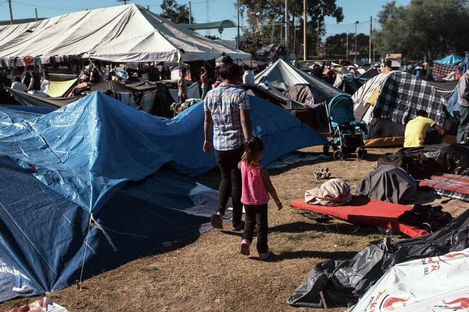 Asylum seekers walk through a makeshift camp near the U.S. and Mexican border crossing in Tijuana, Mexico, on Monday. Photo: Bloomberg Photo By Luis Antonio Rojas / Bloomberg