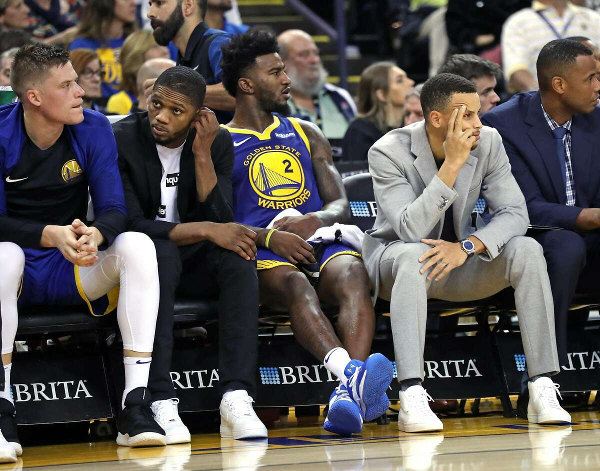Golden State Warriors' Jonas Jerebko, Alfonzo McKinnie, Jordan Bell and Stephen Curry watch as Orlando Magic take a double digit lead in 2nd quarter during NBA game at Oracle Arena in Oakland, Calif. on Monday, November 26, 2018.