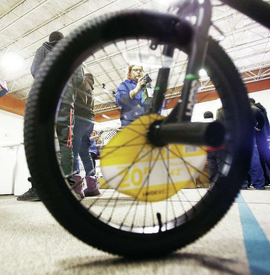 A volunteer from Alton High School, framed through the wheel of a new bicycle, helps sort Community Christmas toys at Main Street United Methodist Church in Alton during last year's Community Christmas drive. Photo: John Badman | The Telegraph