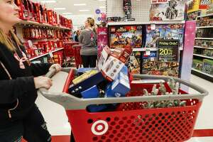 FILE- In this Friday, Nov. 23, 2018, file photo shoppers browse the aisles during a Black Friday sale at a Target store in Newport, Ky. Last year, 65 percent of millennial shoppers put gifts on their credit card. This year, roughly a third of them are still paying off that debt, according to an annual survey of holiday shoppers from NerdWallet. (AP Photo/John Minchillo, File)