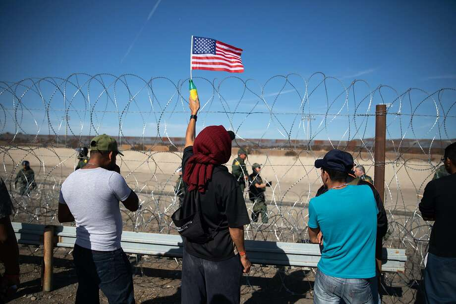 A Central American migrant holds an American flag in front of barbed wire along the U.S.-Mexican border in Tijuana on Nov. 25. Photo: Tomas Ayuso / Bloomberg