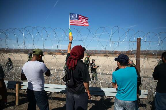 "A Central American migrant holds an American flag in front of barbed wire along the US and Mexico border in Tijuana, Mexico, on Sunday, Nov. 25, 2018. U.S. border officials temporarily closed the San Ysidro port of entry between Tijuana and San Diego, one of the busiest border crossings in the world, ""to ensure public safety."" Photographer: Tomas Ayuso/Bloomberg"