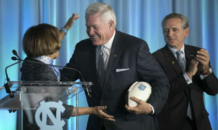 Mack Brown, center, is introduced by University of North Carolina Chancellor Carol Folt, left, as the school's new NCAA college football coach during a news conference, Tuesday, Nov. 27, 2018, at Kenan Stadium in Chapel Hill, N.C. Brown spent 10 seasons at UNC from 1988-97 before leaving for Texas. He left there in 2013 and has been in broadcasting in the years since. (Robert Willett/The News & Observer via AP) Photo: Robert Willett, MBO / Associated Press / 2018, The News & Observer