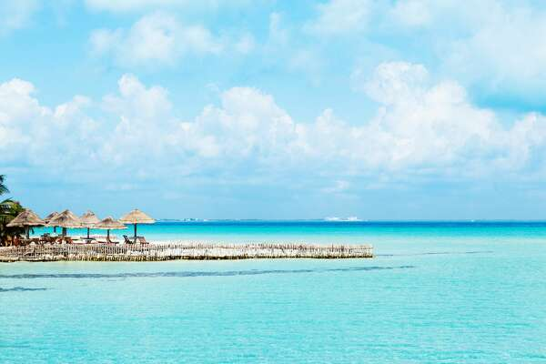 Subject: Horizontal view of the vacation resort hotel on the island of Isla Mujeres, with pristine white sandy beach that face the gentle waves of the aqua blue Caribbean Sea in the glow of morning sunlight.