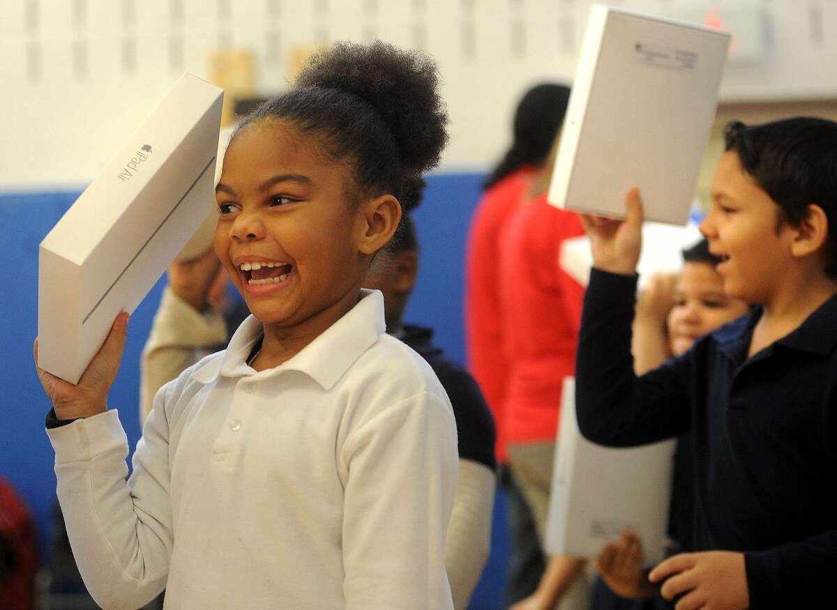 First grader Lucillia Rodriguez can't contain her excitement as she marches in with her new iPad at Roosevelt School in Bridgeport, Conn. on Thursday, January 14, 2016. Roosevelt is one of five Bridgeport schools whose students received the devices as part of a federal Apple Connected grant.