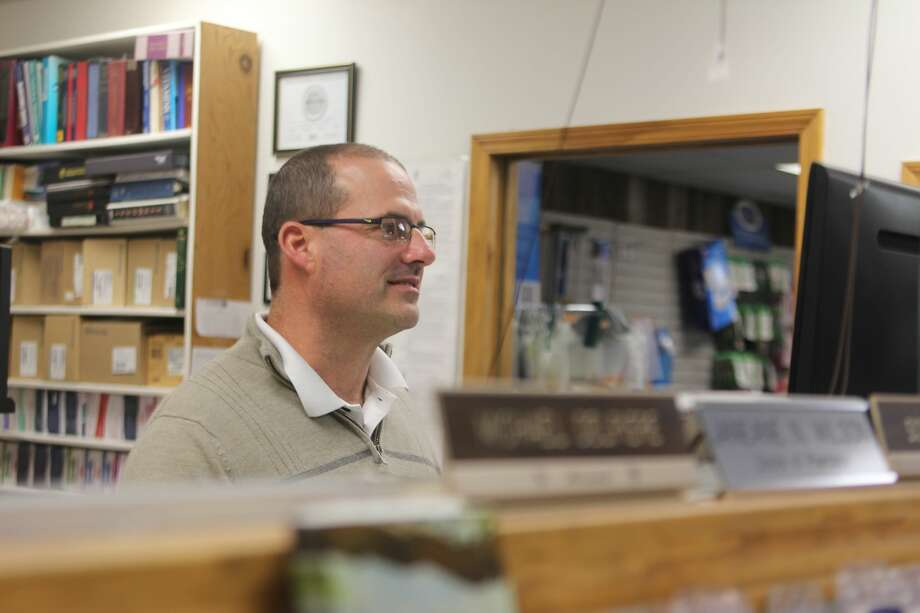 Michael Delpiere, owner of Harbor Drug in Harbor Beach, works behind the pharmacy counter during a busy afternoon.