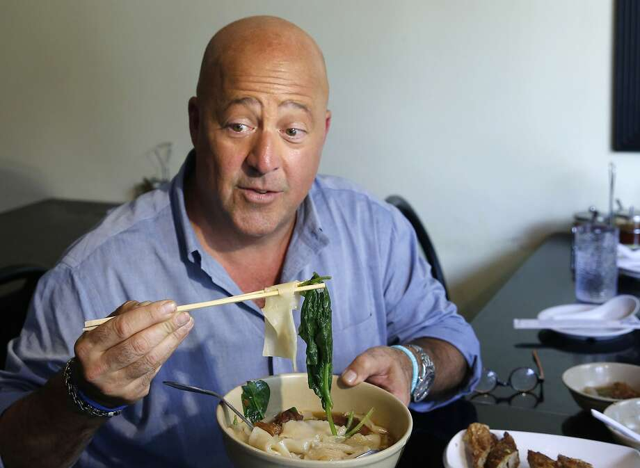 "In this 2017 file photo, Travel Channel's ""Bizzare Foods"" host Andrew Zimmern samples Taiwanese noodle soup at Happy Stony Noodle in Elmhurst, Queens in New York. Zimmern is apologizing for his comments about Chinese restaurants after he was criticized as culturally insensitive. Photo: Kathy Willens / Associated Press"