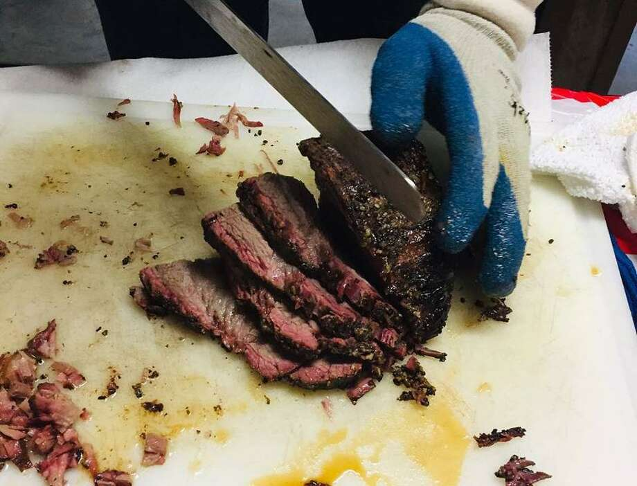 Pitmaster Christopher Haynes cuts some slices of brisket at 1836 BBQ. Photo: 1836 BBQ
