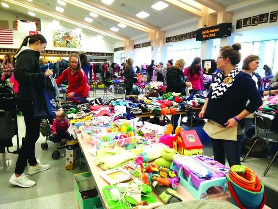 In this March 2017 file photo, shoppers browse tables of clothing and toys last year in the Edwardsville High School Commons at one of the Edwardsville/Glen Carbon Junior Service Club's annual events. The club will host its biennial Holiday House Tour where homeowners graciously open their beautifully decorated homes and invite the public to take a tour for the holidays Photo: Marci Winters-McLaughlin | For The Intelligencer