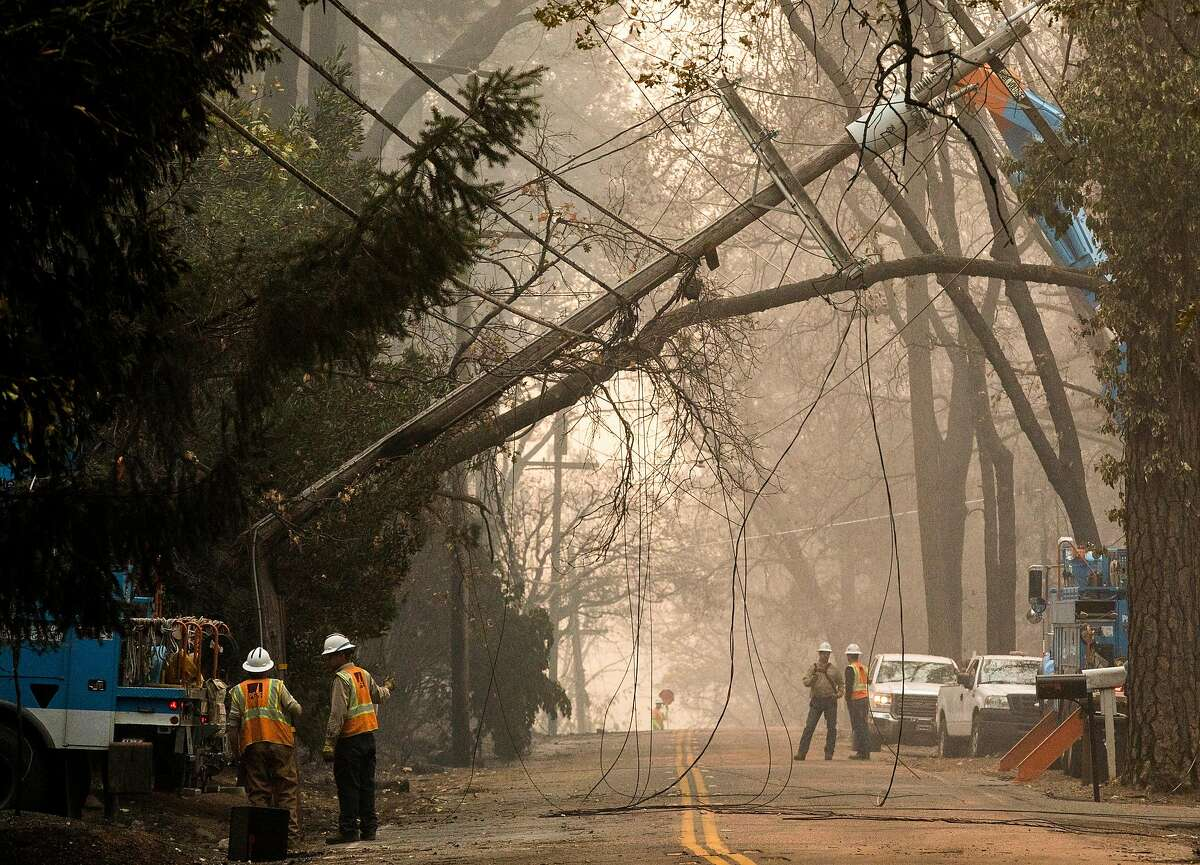 PG workers take down a downed telephone pole after the Camp Fire devastated the entire town of Paradise, Calif. Saturday, Nov. 10, 2018. A new report from the California Public Utilities Commission concluded the utility's failure to maintain a nearly century-old power line sparked the blaze that led to the fire, which resulted in 85 deaths.