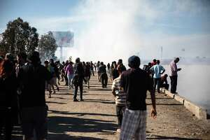 """Tear gas fired by U.S. Customs and Border Protection (CBP) officers rises as Central American migrants gather near the US and Mexico border in Tijuana, Mexico, on Sunday, Nov. 25, 2018. U.S. border officials temporarily closed the San Ysidro port of entry between Tijuana and San Diego, one of the busiest border crossings in the world, """"to ensure public safety."""" Photographer: Tomas Ayuso/Bloomberg"""