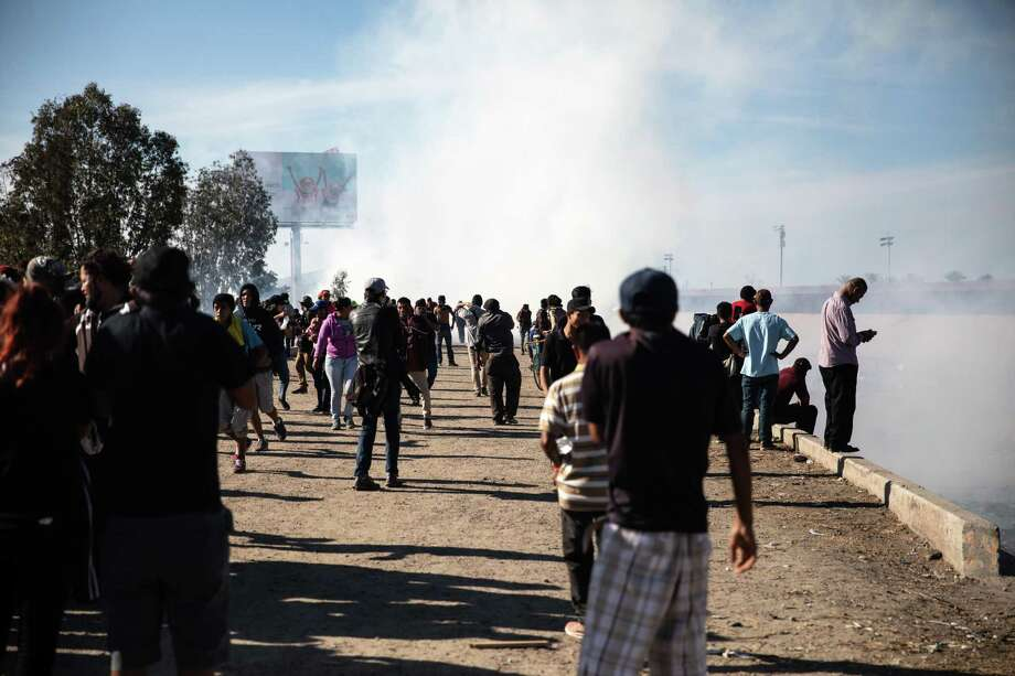 "Tear gas fired by U.S. Customs and Border Protection (CBP) officers rises as Central American migrants gather near the US and Mexico border in Tijuana, Mexico, on Sunday, Nov. 25, 2018. U.S. border officials temporarily closed the San Ysidro port of entry between Tijuana and San Diego, one of the busiest border crossings in the world, ""to ensure public safety."" Photographer: Tomas Ayuso/Bloomberg Photo: Tomas Ayuso / Bloomberg / © 2018 Bloomberg Finance LP"