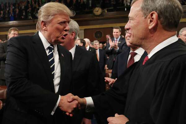 """President Donald Trump shakes hands with US Supreme Court Chief Justice John Roberts as Trump arrives to deliver his first address to a joint session of Congress last year. Roberts issued an extraordinary rebuke of Trump on Nov. 21 after the president criticized a ruling he said was handed down by an """"Obama judge."""" """"We do not have Obama judges or Trump judges, Bush judges or Clinton judges,"""" Roberts said in a statement to the Associated Press."""