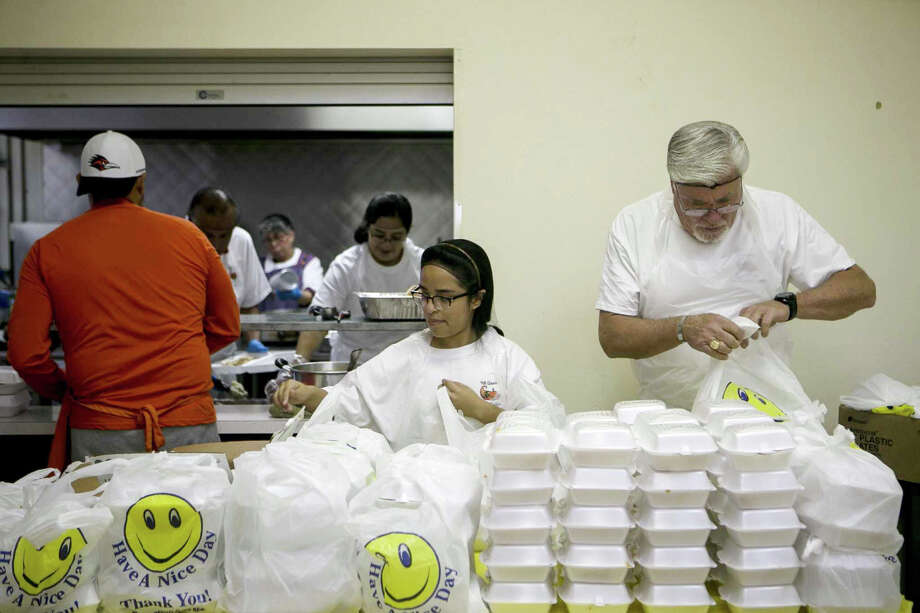 Brianna Lomas and Kent Farquhar prepare to-go meals during the annual Thanksgiving lunch held by the Martinez family in honor of their late mother, Angie Martinez, at St. Jude Catholic Church on San Antonio's West Side Thursday, Nov. 22, 2018. Angie Martinez wanted to do something to help those in need in her parish around Thanksgiving and began donating frozen turkeys before her death in 2010. Following her death, her family expanded the tradition by offering a full traditional lunch for the community and last year they fed around 300 individuals. Photo: Josie Norris,  Staff / San Antonio Express-News / © San Antonio Express-News