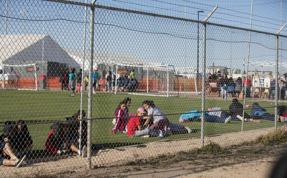CORRECTS TO CLARIFY TEENS WERE NOT LOOKING AT PROTESTERS AS THERE WERE NOT PROTESTS THAT DAY - In this Nov. 25, 2018 photo provided by Ivan Pierre Aguirre, migrant teens held inside the Tornillo detention camp sit inside the facility in Tornillo, Texas. The Trump administration announced in June 2018 that it would open the temporary shelter for up to 360 migrant children in this isolated corner of the Texas desert. Less than six months later, the facility has expanded into a detention camp holding thousands of teenagers - and it shows every sign of becoming more permanent. (Ivan Pierre Aguirre via AP) Photo: Ivan Pierre Aguirre / Associated Press