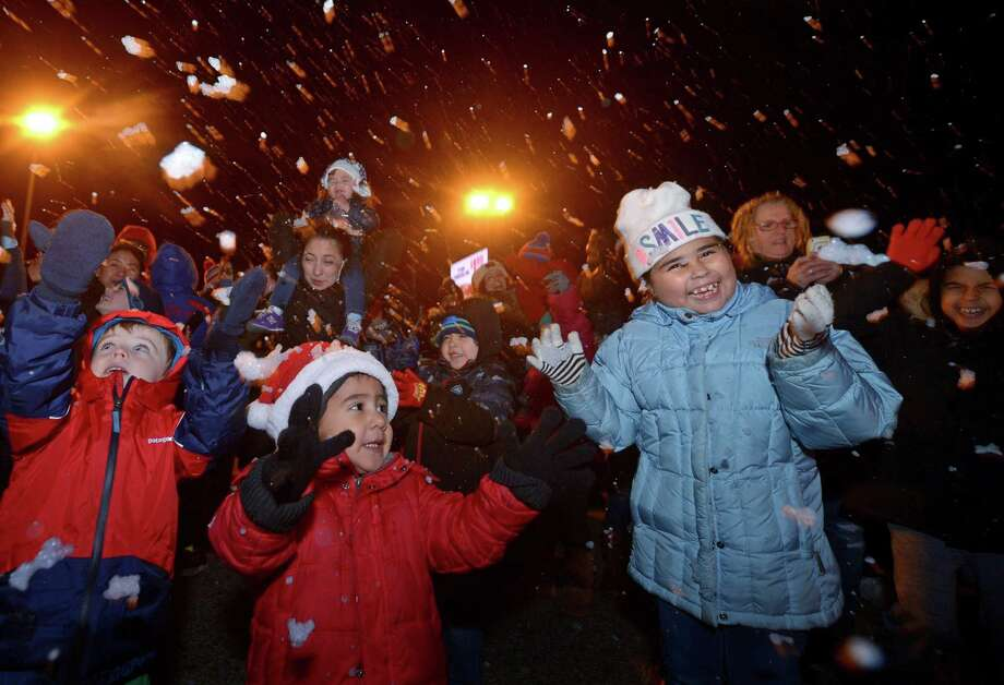 Children including Giavanna Buckner, 9, of Norwalk, right, rejoice in the fake snow during Stew Leonard's annual Christmas Tree Lighting celebration Tuesday, November 27, 2018, at the store in Norwalk, Conn. The festivities began with plenty of musical entertainmentand ended with Santa spending the evening mingling with children and handing out candy canes. For the third year, a 30-foot artificial evergreen tree will serve as the Norwalk store's holiday centerpiece. Created by American Christmas, Inc., the tree is hand-crafted by seven people over the course of a month. Once at Stew's it took 15 people more than 11 hours to put it up and string more than 33,000 LED multi-color lights. The artificial tree can be recycled at the end of their 6-year lifespan. Photo: Erik Trautmann / Hearst Connecticut Media / Norwalk Hour