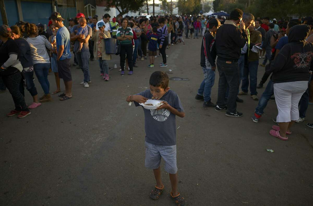 A boy eats as others wait in line for dinner outside of a shelter housing members of the migrant caravan, Monday, Nov. 26, 2018, in Tijuana, Mexico. A day after a march by members of the migrant caravan turned into an attempt to breach the U.S. border with Mexico, many migrants appeared sullen Monday, wondering whether the unrest had spoiled whatever possibilities they might have had for making asylum cases. (AP Photo/Gregory Bull)