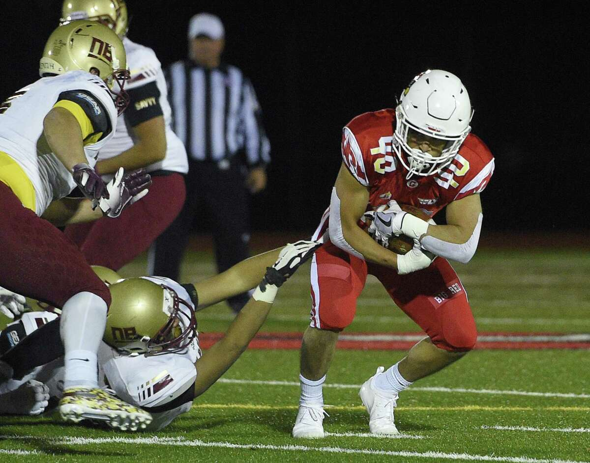 Greenwich running back Tysen Comizio (40) sheds a tackle against New Britain during the Class LL quarterfinals on Tuesday night at Greenwich High Schoo.