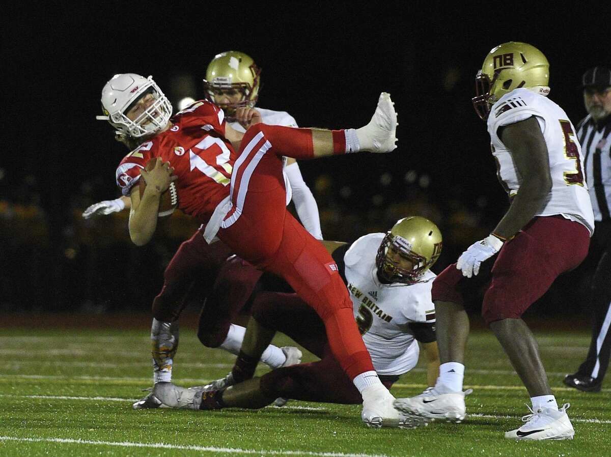 Greenwich quarterback Gavin Muir (12) breaks free against New Britain during a Class LL quarterfinal game on Tuesday night at Greenwich High School. The Cardinals won 49-13 and will play host to Newtown on Sunday in the semifinals.