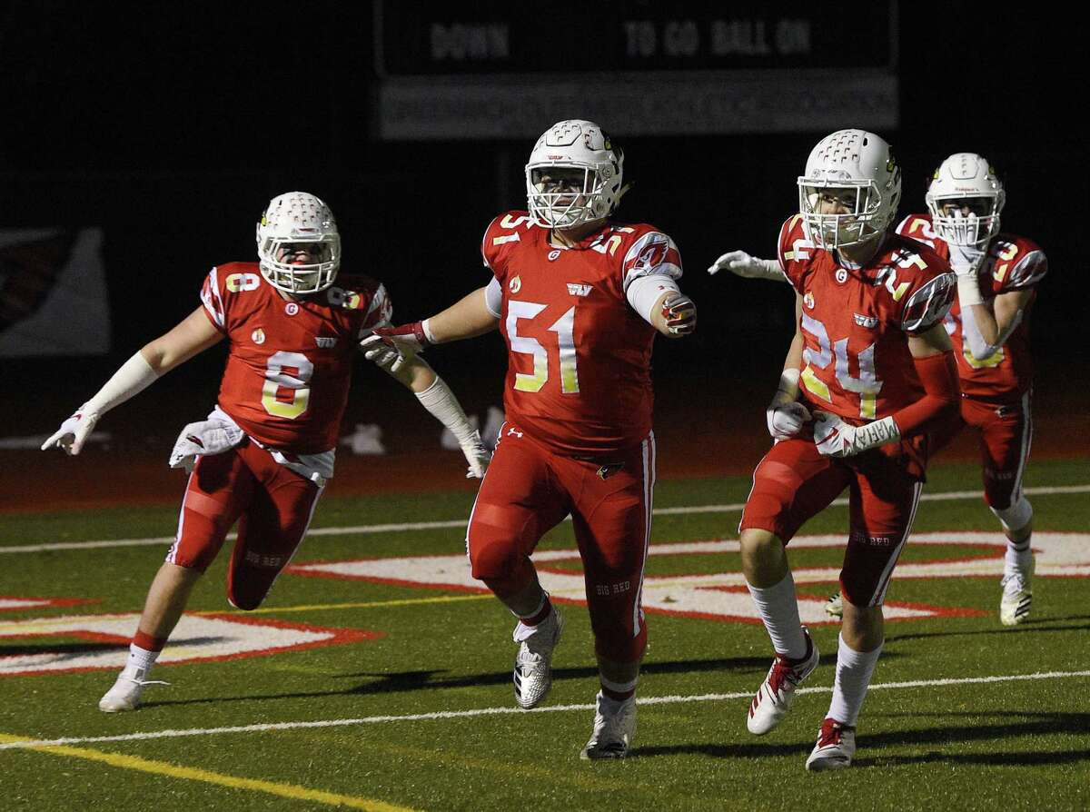 Greenwich's Jack Feda (8), Joe Kranginger (51) and Nick Veronis (24) celebrate a fumble recovered for a touchdown against New Britain on Tuesday night at Greenwich High School.