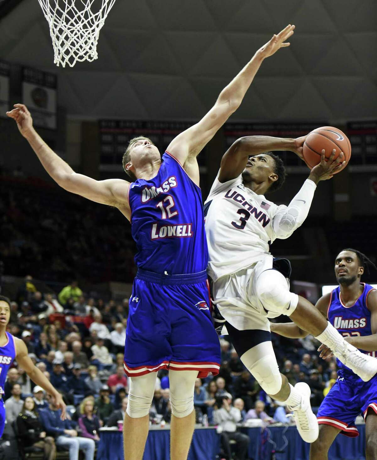 UConn's Alterique Gilbert (3) goes up against UMass-Lowell's Sesan Russell (2) during the first half of an NCAA college basketball game, Tuesday, Nov. 27, 2018, in Storrs, Conn. (AP Photo/Stephen Dunn)