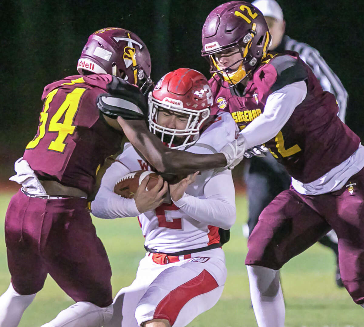 (John Vanacore/For Hearst Connecticut Media) Sheehan defenders Kyle Simmons(12) and Terrence Bogen(34) stop Wolcott running back Anthony Ligi after a short gain during the Titan's CIAC Class M quartfinal win Tuesday.