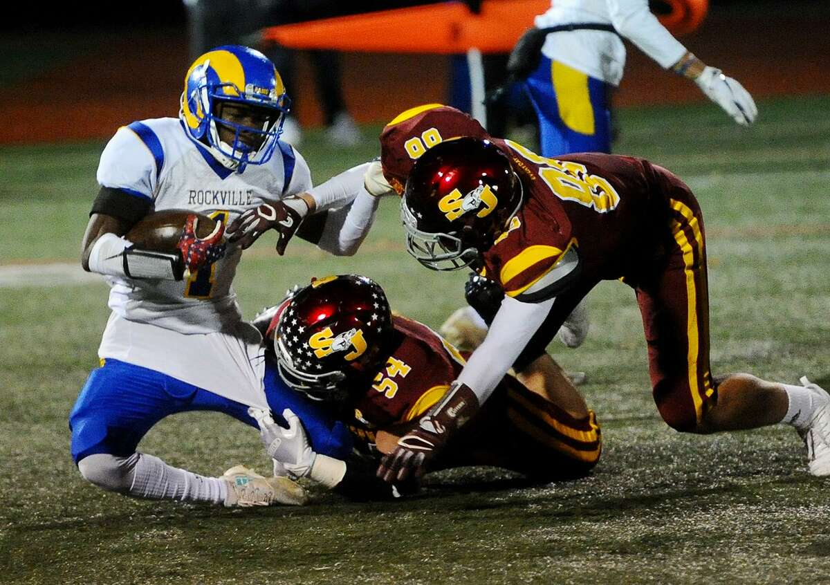 From left; Rockville's Kejuan Greene is taken down in the backfield by St. Joseph's Alex Pagliarini and Owen DaSilva in the first half of the Cadets' blow out victory in the Class M football quarterfinals at Penders Field in Stratford, Conn. on Tuesday, November 27, 2018.