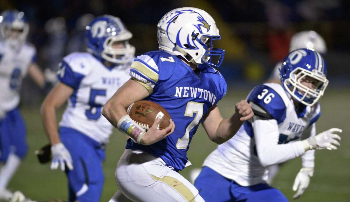 Newtown's Dan Mason (7) races down the field with Darien's James Morrissey (36) in pursuit during a Class LL quarterfinal game Tuesday at Newtown High School.