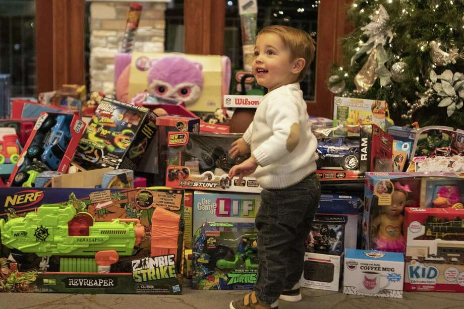Christian Besong points towards one of the toys collected during Christmas with the Commissioner on Tuesday at The Woodlands Country Club Palmer Course. Photo: Cody Bahn, Houston Chronicle / Staff Photographer / © 2018 Houston Chronicle