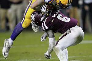 LSU tight end Foster Moreau (18) goes over Texas A&M defensive back Donovan Wilson (6) to score a touchdown during the second half of an NCAA college football game Saturday, Nov. 24, 2018, in College Station, Texas. Texas A&M won 74-72 in seven overtimes.(AP Photo/David J. Phillip)