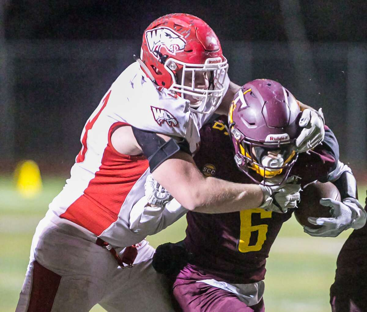 (John Vanacore/For Hearst Connecticut Media) Sheehan's Jake Smith battles for yardage against Wolcott defensive tackle Dean Howell during their CIAC Class M quarterfinal game in Wallingford Tuesday.