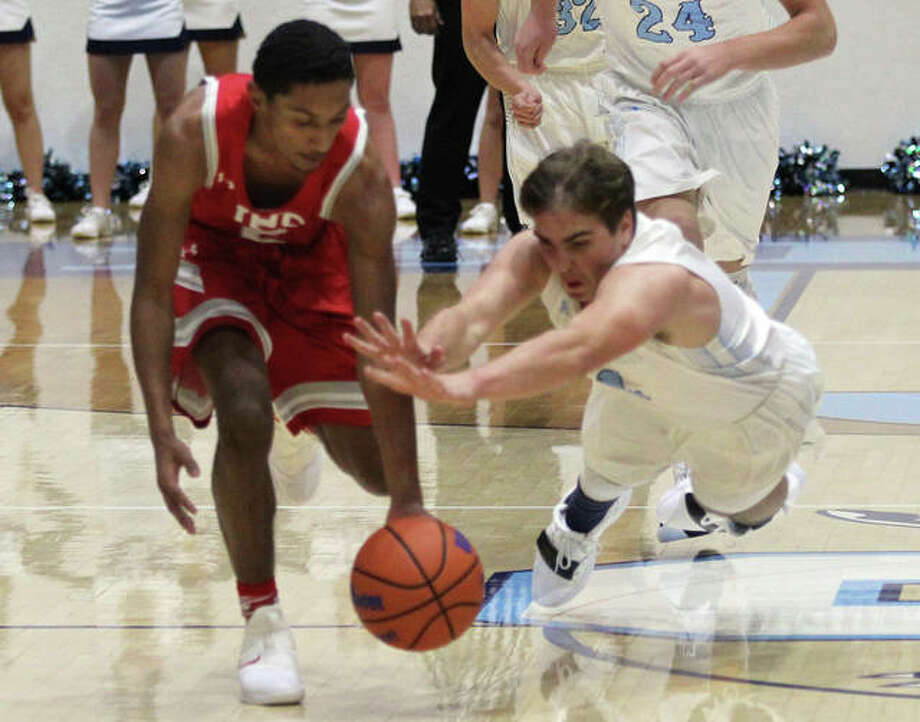 Jersey's David Rogers (right) dives in a race with Jacksonville's Jordan White to a loose ball during the first half of the Panthers' victory on Tuesday night at Havens Gym in Jerseyville. Photo: Greg Shashack / The Telegraph