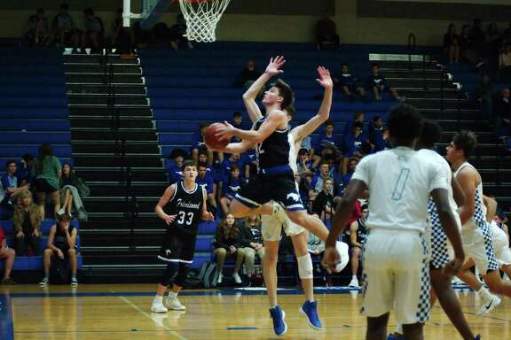 Friendswood's Ian Bivins (12) drives to the basket past Clear Springs' Kyle Burt (0) Tuesday at Clear Springs High School.
