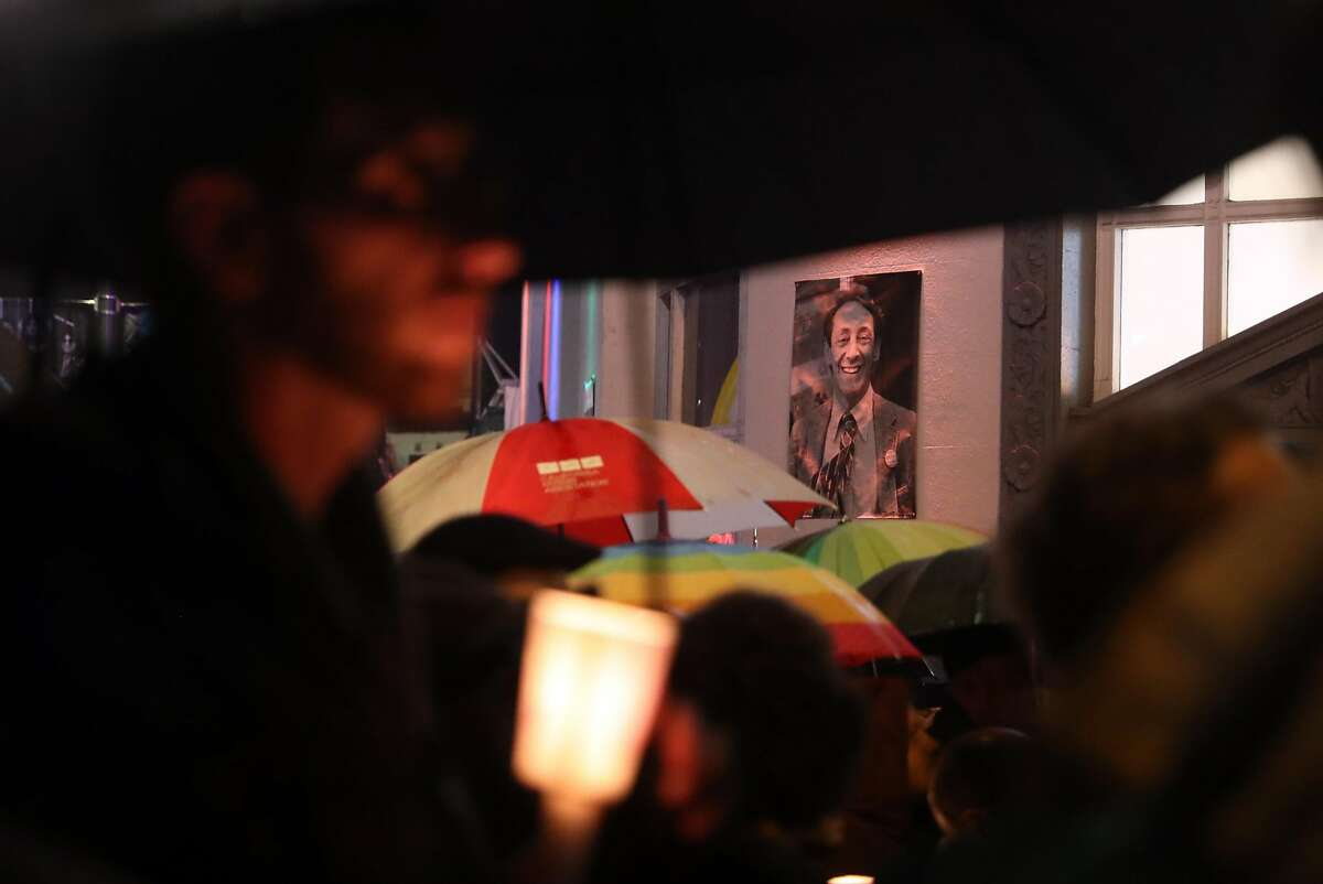 A photograph of Harvey Milk hangs above the crowd during gathering before annual candlelight walk from The Castro to City Hall in memory of Harvey Milk and Mayor George Moscone, who were slain 40 years ago in San Francisco, Calif.. Photographed on Tuesday, November 27, 2018.