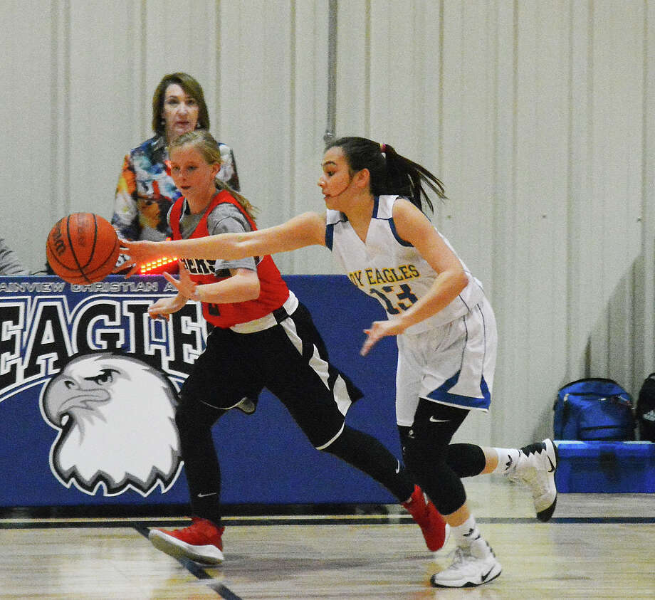 PICKING POCKETS  Plainview Christian Academy junior guard Andrea Lara pokes the ball away from Sharp Academy guard Kiersten Hull for one of her 12 steals during girls basketball action on Tuesday night in Plainview. The Lady Eagles beat the Lady Sabres, 73-7. Photo: Alexis Cubit/Plainview Herald