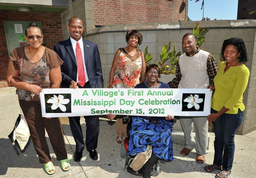 A Village organizers, from left, Clara Phillips Mark Bobb-Semple, Anne Pope, Bessie Thompson, Willie White, and Noelene Smith pose outside 3 Lincoln Square in Albany Thursday Sept. 13, 2012, with a banner for this Saturday's Mississippi Day Celebration. (John Carl D'Annibale / Times Union)
