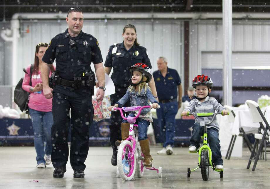 Corbin Hess, 3, rides his new bike next to his sister Makenzie Stone, 5, during Montgomery County Sheriff's inaugural Operation Blue Elf Christmas toy drive at the Montgomery County Convention and Expo Center, Wednesday, Dec. 20, 2017, in Conroe. Photo: Jason Fochtman, Staff Photographer / Houston Chronicle / © 2017 Houston Chronicle