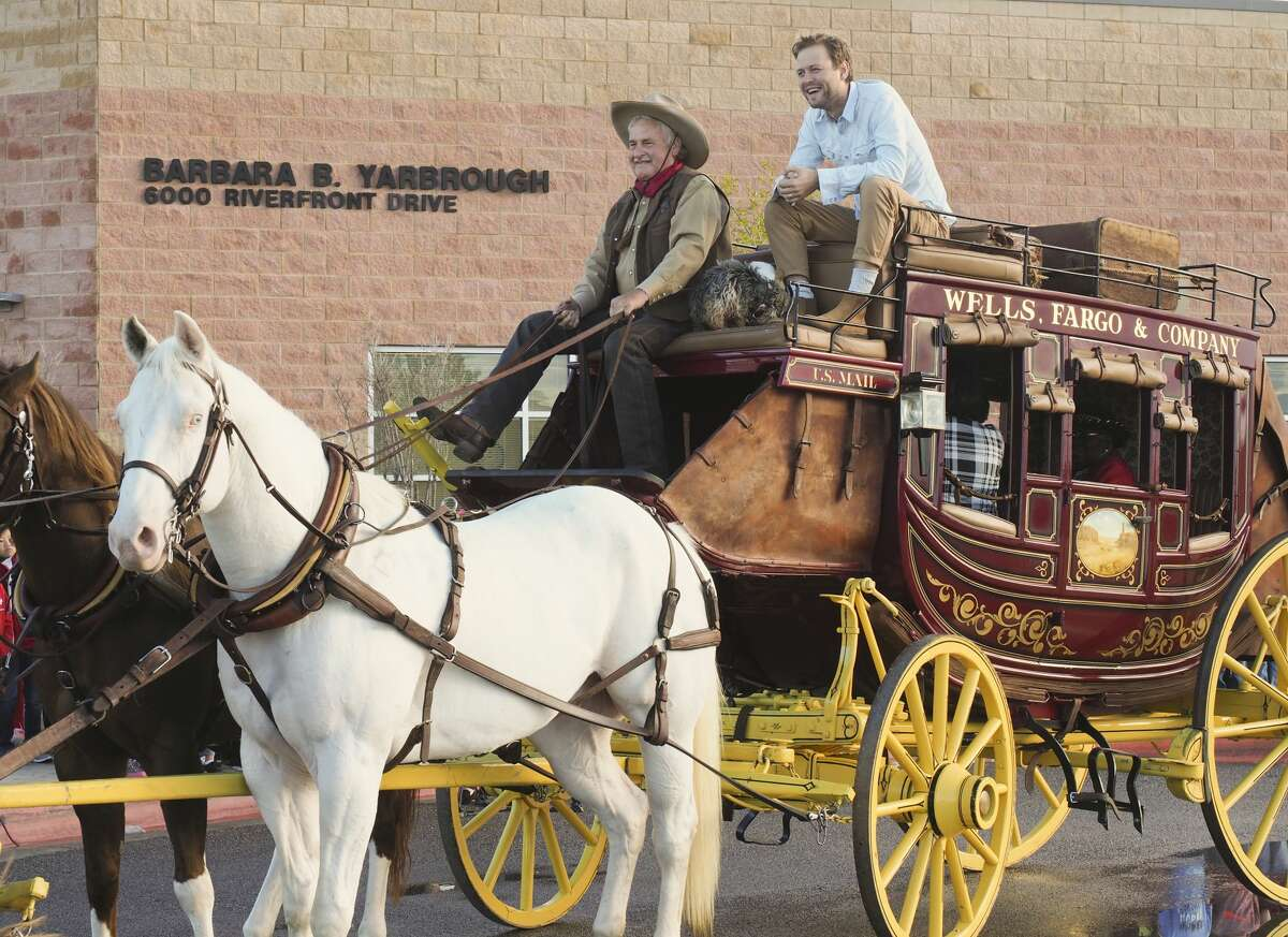 Author Marc Barnett, right, rides atop a Wells Fargo stagecoach bound for Yarbrough Elementary School on Oct. 9 to kick off Project Literacy 2018. Riding in the stagecoach are Yarbrough students and the school's namesake, retired teacher Barbara Yarbrough.