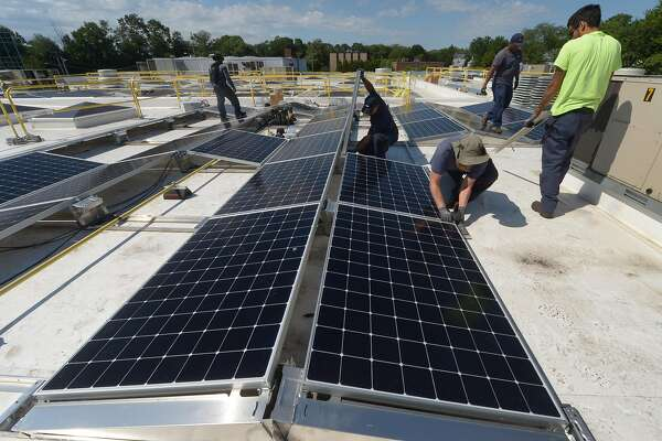ENCON employees install solar panels on the roof of the Paul Miller Nissan dealership in Fairfield, which has installed the solar-energy array with financing from Darien-based Greenworks Lending, Wednesday, July 18, 2018, in Fairfield, Conn.