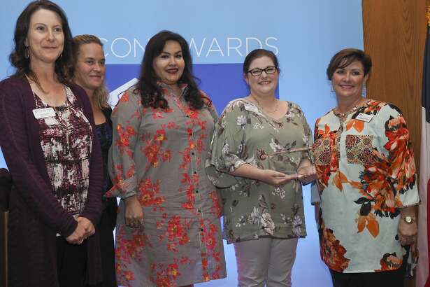 Amy Hendrick, right, 2018 Beacon Awards chair, presents the Excellence in Technology Award to members of Midland Need to Read.