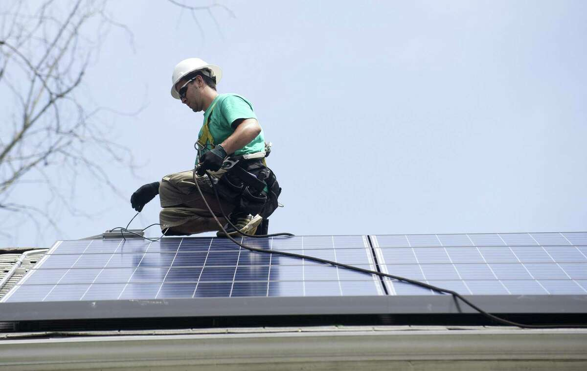 A Solar City installer works in 2013 on an installation in Greenwich, Conn. Five years later, Connecticut is expected to close out 2018 passing by the 500-megawatt mark for photovoltaic installations statewide, sufficient to power the equivalent of about 70,000 homes according to estimates by the Solar Energy Industries Association.
