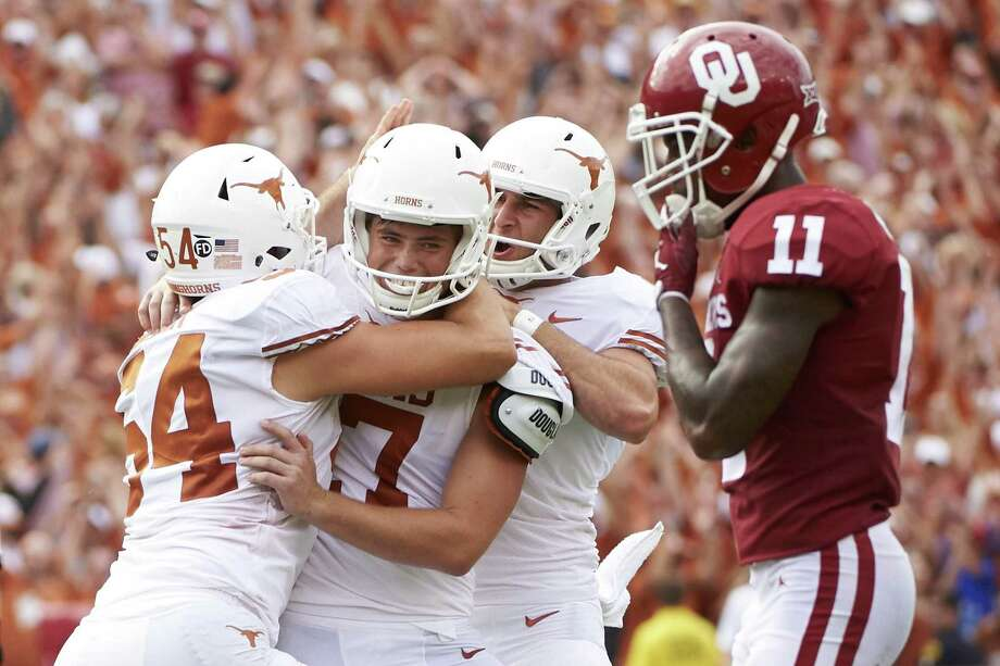 In this Oct. 6, 2018, file photo, Texas kicker Cameron Dicker (17) celebrates with teammates after kicking the game-winning field goal in the closing seconds of the second half of an NCAA college football game against Oklahoma at the Cotton Bowl in Dallas. The Texas-Oklahoma rivalry is never short on bad blood between the Big 12 border states. Photo: Cooper Neill, FRE / Associated Press / Copyright 2018 The Associated Press. All Rights Reserved.