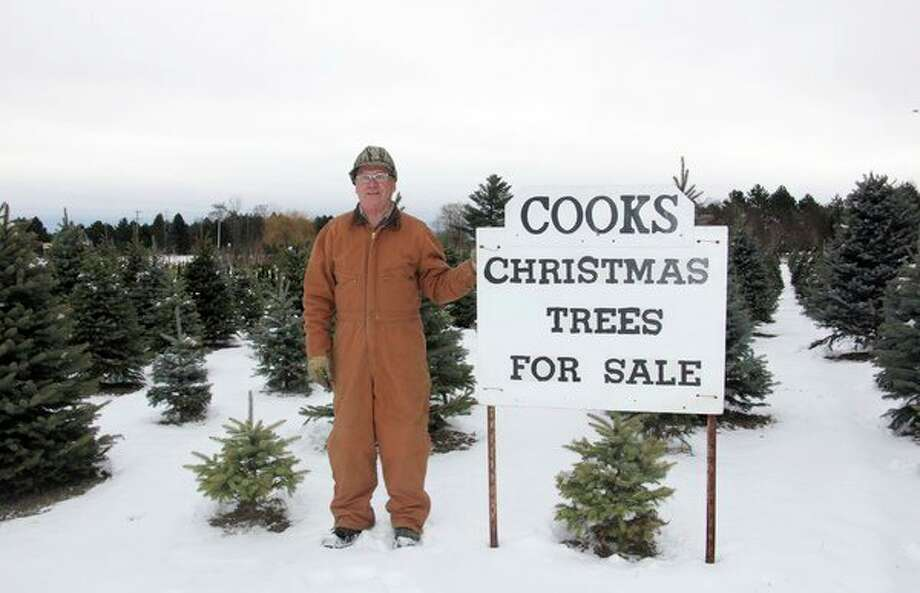 Hilary Cook, owner of Cook's Tree Sales, poses with only a small portion of Christmas trees his farm has to offer. Following more than 30 years of service, this will be the final season of business for Cook and his wife, Marie. Cook's Tree Sales is located at 51 S. Verona Road in Bad Axe and open weekdays from 1 p.m. to dark and from 10:30 a.m. until dark on the weekends. (Bradley Massman/Huron Daily Tribune)