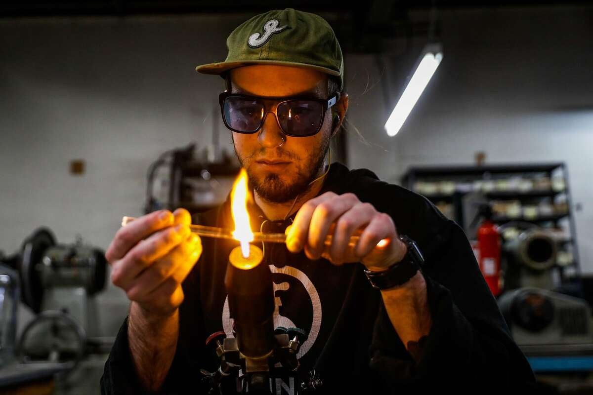 Sam Merkel (left) heats up glass at Adams & Chittenden, a 25-year-old scientific glass blowing company in Berkeley, California, on Tuesday, Nov. 27, 2018.