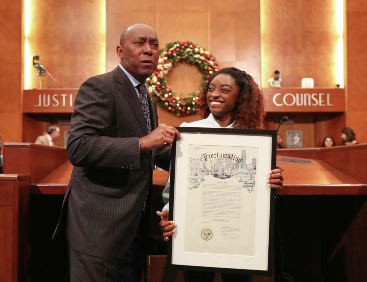 """Mayor Turner makes Simone Biles laugh after declaring Tuesday, Nov. 27 as """"Simone Biles Day"""" and presented her with a proclamation and key to the City of Houston Tuesday, Nov. 27, 2018, in Houston. Biles came to the ceremony with her mother, Nellie Biles."""