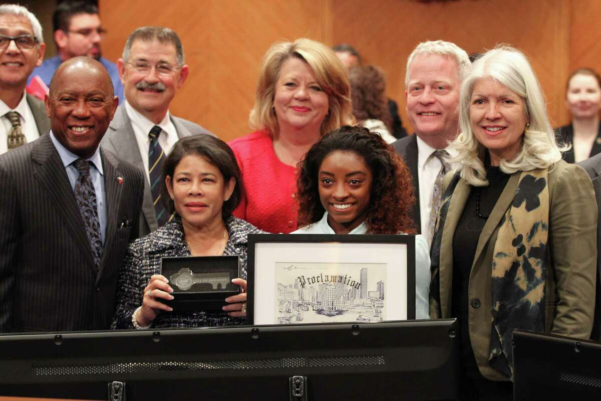 """Mayor Turner declared Tuesday, Nov. 27 as """"Simone Biles Day"""" and present the her with a proclamation and key to the City of Houston Tuesday, Nov. 27, 2018, in Houston. Biles,(second from right) and her mother, Nellie Biles (second from left) had their photo taken with the mayor and the city council during the ceremony."""