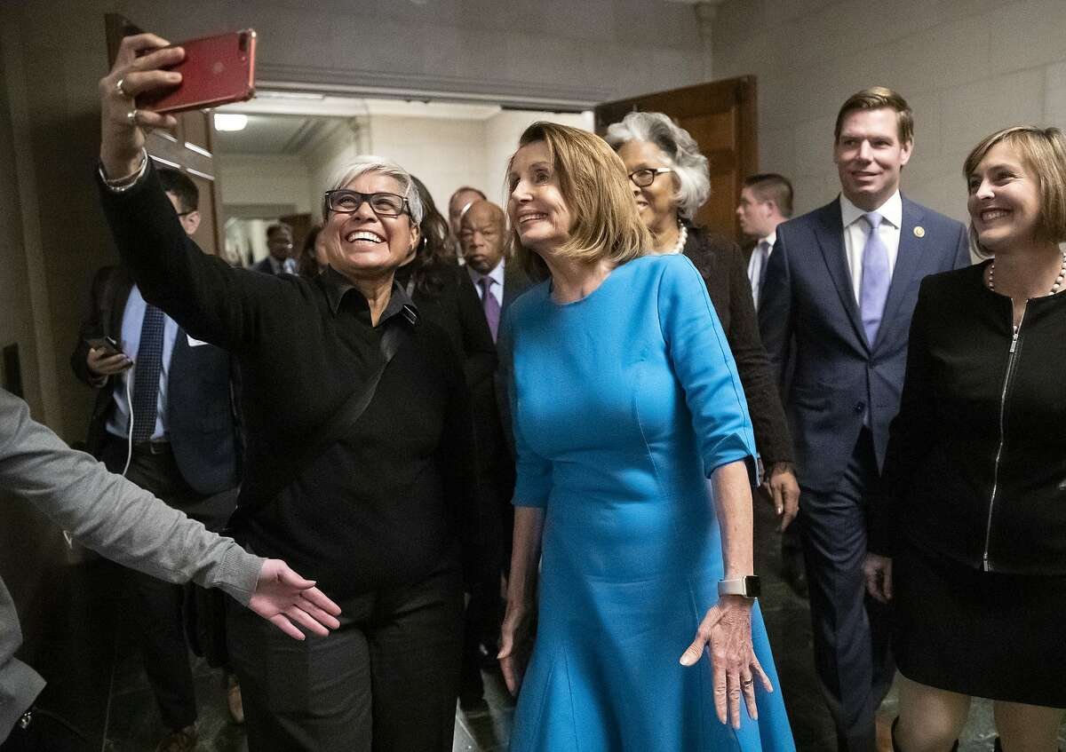 Carmen Guzman, left, a former congressional staffer from McLean, Va., snaps a selfie with Democratic Leader Nancy Pelosi of California, center, as she emerged victorious from the House Democratic leadership elections as the choice for speaker of the House when her party takes power as the majority in the 116th Congress, on Capitol Hill in Washington, Wednesday, Nov. 28, 2018. She still faces a showdown vote for House speaker when lawmakers convene in January. (AP Photo/J. Scott Applewhite)